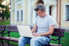 Hombre joven con el ordenador portátil que se sienta en el parque Gente, tecnología co fotografía de archivo