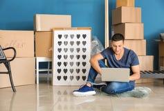 Hombre joven con el ordenador portátil que se sienta en piso cerca de las cajas y de las pertenencia dentro El trasladarse a nuev foto de archivo libre de regalías