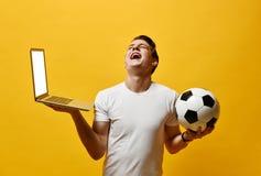 Hombre joven con el ordenador port?til y un bal?n de f?tbol imagen de archivo libre de regalías
