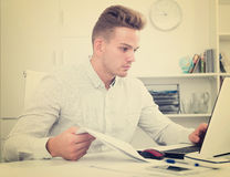 Hombre joven con el ordenador portátil en oficina Imagen de archivo libre de regalías