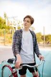 Hombre joven con el pelo rubio que se coloca en pantalones cortos y camisa sport con la bicicleta roja en la cancha de básquet Mu Fotografía de archivo libre de regalías