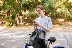 Hombre joven con el pelo rubio que se coloca con la mochila y la bicicleta en parque Refresque la situación sonriente del muchach Imagen de archivo libre de regalías