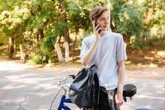 Hombre joven con el pelo rubio que se coloca con la mochila y la bicicleta y que mira soñador a un lado mientras que habla en su  Fotos de archivo libres de regalías