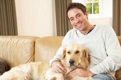Hombre joven con el perro que se sienta en el sofá Foto de archivo