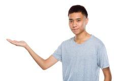 Hombre joven con el presente de la mano Imagenes de archivo