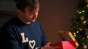Hombre joven con el regalo de Navidad en las manos que lo abren que se sienta en el sofá almacen de video