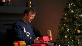 Hombre joven con el regalo de Navidad en las manos que lo abren que se sienta en el sofá almacen de metraje de vídeo