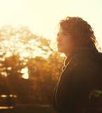 Hombre joven con el retrato del pelo rizado en parque del otoño en una puesta del sol Fotos de archivo