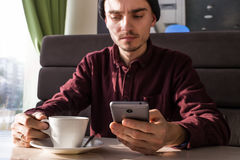 Hombre joven con el smartphone que come café en el café Imagenes de archivo