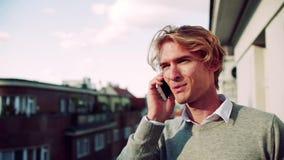 Hombre joven con el smartphone que se coloca en un balcón en la ciudad, haciendo una llamada de teléfono almacen de metraje de vídeo