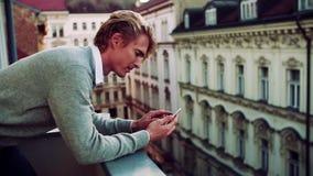 Hombre joven con el smartphone que se coloca en un balcón en la ciudad, mandando un SMS metrajes