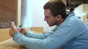 Hombre joven con el smartphone que se sienta en café almacen de metraje de vídeo