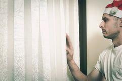 Hombre joven con el sombrero de Santa Claus que mira a través de la ventana que siente sola y triste para concepto de la depresió Imagenes de archivo