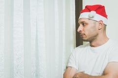 Hombre joven con el sombrero de Santa Claus que mira a través de la ventana que siente sola y triste para concepto de la depresió Foto de archivo