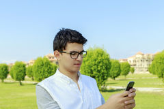 Hombre joven con el teléfono elegante a disposición, al aire libre Foto de archivo libre de regalías