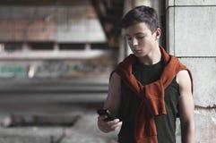 Hombre joven con el teléfono en el edificio viejo Imagen de archivo libre de regalías