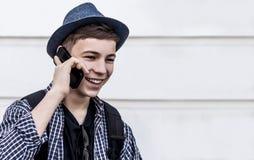 Hombre joven con el teléfono en el fondo blanco de la pared Imagen de archivo