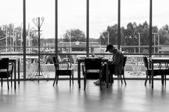 Hombre joven con el teléfono en la tabla cerca de la ventana Foto de archivo libre de regalías