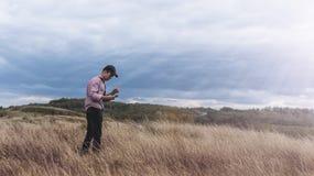 Hombre joven con el teléfono en una alta colina Imagen de archivo libre de regalías