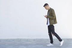 Hombre joven con el teléfono móvil Fotografía de archivo libre de regalías