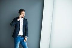 Hombre joven con el teléfono móvil por la pared Fotos de archivo libres de regalías