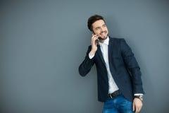 Hombre joven con el teléfono móvil por la pared Fotografía de archivo libre de regalías