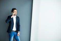 Hombre joven con el teléfono móvil por la pared Imágenes de archivo libres de regalías