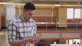 Hombre joven con el teléfono que manda un SMS al colega, edificio interior metrajes