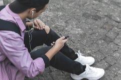 Hombre joven con el teléfono que se sienta en la acera Imagen de archivo