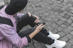 Hombre joven con el teléfono que se sienta en la acera Fotografía de archivo libre de regalías
