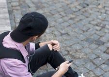 Hombre joven con el teléfono que se sienta en la acera Fotografía de archivo