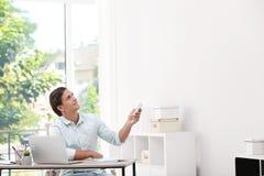 Hombre joven con el telecontrol c del acondicionador de aire foto de archivo libre de regalías