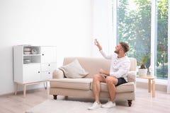 Hombre joven con el telecontrol del acondicionador de aire imagenes de archivo