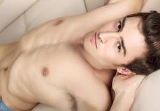 Hombre joven con el torso desnudo que miente en un sofá blanco Imagenes de archivo