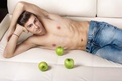 Hombre joven con el torso desnudo que miente en un sofá blanco Foto de archivo