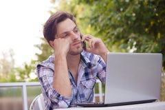 Hombre joven con el trabajo del smartphone y del ordenador portátil al aire libre foto de archivo