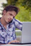 Hombre joven con el trabajo del smartphone y del ordenador portátil al aire libre imagenes de archivo