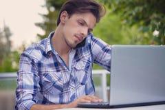 Hombre joven con el trabajo del smartphone y del ordenador portátil al aire libre fotografía de archivo libre de regalías