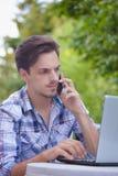Hombre joven con el trabajo del smartphone y del ordenador portátil al aire libre fotografía de archivo