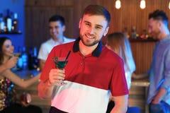 Hombre joven con el vidrio del c?ctel de martini fotografía de archivo libre de regalías
