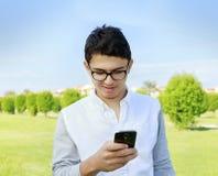 Hombre joven con gafas en el jardín que mira en teléfono elegante Fotografía de archivo
