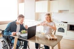 Hombre joven con integraci?n y necesidades especiales que come la ensalada en cocina Si?ntese en la silla de ruedas y estudiar La imagen de archivo libre de regalías