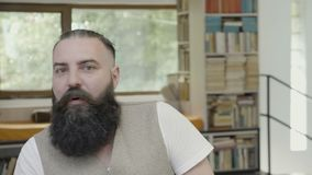 Hombre joven con la barba que es sorprendido y chocado teniendo una reacción divertida del omg - almacen de metraje de vídeo