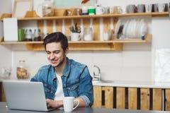 Hombre joven con la barba que trabaja en el ordenador portátil Imagen de archivo