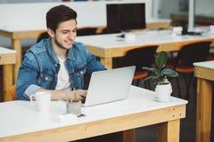 Hombre joven con la barba que trabaja en el ordenador portátil Fotos de archivo libres de regalías