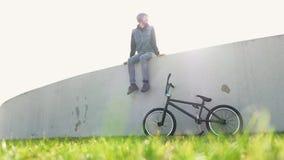 Hombre joven con la bicicleta en la hierba verde que se sienta en luz trasera que escucha la música