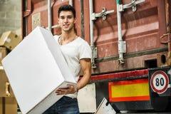 Hombre joven con la caja blanca grande en tren de carga Imagen de archivo libre de regalías