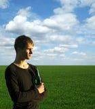 Hombre joven con la cerveza en campo verde bajo el cielo azul Imagen de archivo