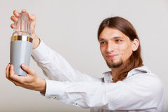 Hombre joven con la coctelera que hace que el cóctel bebe Fotografía de archivo