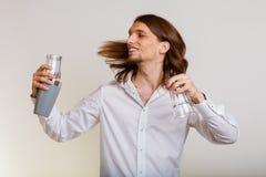 Hombre joven con la coctelera que hace que el cóctel bebe Foto de archivo